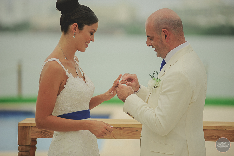 Grooms rings are put on the ceremony on the beach